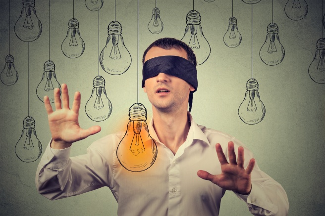 Blindfolded young man walking through light bulbs searching for bright idea